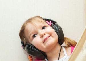 Little beautiful girl in headphones listens to music
